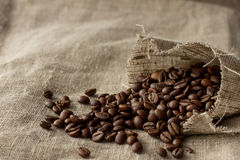 Coffee beans spread from linen pocket. Selective focus Stock Photography