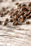 Coffee beans sprinkled on a textured rustic wooden boards Stock Photo