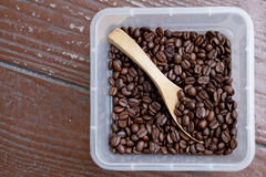 Coffee beans, square shaped box with wooden spoon. Wooden surfac Stock Image