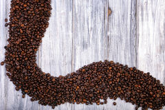 Coffee beans stacked  on the old wooden background Stock Photos