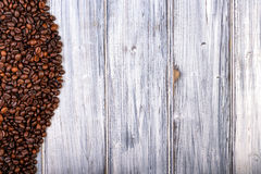 Coffee beans stacked  on the old wooden background Royalty Free Stock Photos