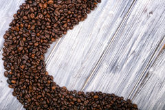 Coffee beans stacked  on the old wooden background Stock Image