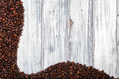 Coffee beans stacked  on the old wooden background Stock Images