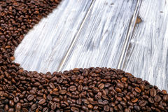 Coffee beans stacked  on the old wooden background Royalty Free Stock Photography