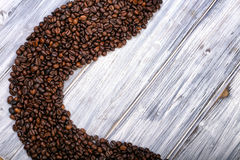 Coffee beans stacked  on the old wooden background Royalty Free Stock Images