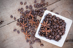 Coffee beans and star anise in a white bowl on wooden background Royalty Free Stock Images