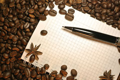 Coffee beans, stars anise, pen and notebook royalty free stock photo