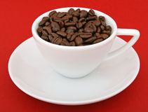 Coffee beans - Stimulant drug for home and office. Cup of coffee beans, isolated on red, macro closeup, close-up with copy space Stock Photo