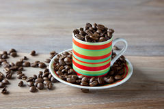 Coffee beans in striped cup Royalty Free Stock Photography
