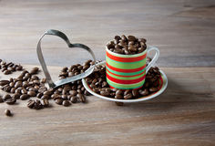 Coffee beans in striped cup Royalty Free Stock Photos