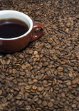 Coffee beans surrounding a cup Stock Image
