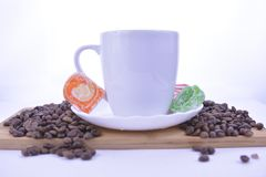 coffee beans and sweets on the table, white cup of coffee on a s stock image