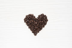 Coffee beans on a table in heart shape shot on white wooden. Background Stock Images