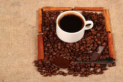 Coffee beans and teaspoon of ground coffee with chocolate bars. And cinnamon sticks as background for a cup of fragrant hot coffee Stock Images