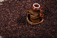 Coffee beans and three cups Royalty Free Stock Photos