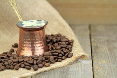 Coffee beans and traditional Turkish copper coffee pot on a burlap Stock Images