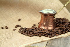 Coffee beans and traditional Turkish copper coffee pot on a burlap Stock Photos
