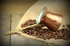 Coffee beans and traditional Turkish copper coffee pot on a burlap Stock Photo