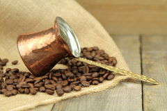 Coffee beans and traditional Turkish copper coffee pot on a burlap Royalty Free Stock Photos
