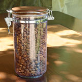 Coffee beans in transparent glass container on wooden table. Royalty Free Stock Image