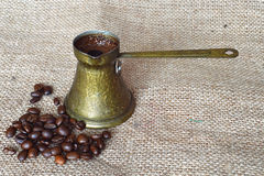 Coffee beans and Turkish coffee in a traditional copper  coffee pot Stock Photo