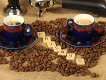 Coffee beans, two ornate cups, tamper and group handle with the letters friends on a hessian backgroun. D, Melbourne 2017 royalty free stock photography