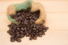 Coffee beans in the vintage bag. On the brown background stock image