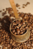 Coffee beans and vintage copper turkish coffee pot (cezve or ibrik) on the cloth sack. Coffee beans, vintage copper turkish coffee pot (cezve or stock photos