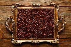 Coffee beans in vintage golden tray on wood Royalty Free Stock Photo