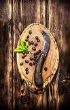 Coffee beans with vintage knife. On the saw cut of wood. On wooden background Royalty Free Stock Photos
