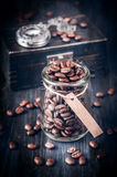 Coffee beans and vintage watch on a chain on a wooden background Royalty Free Stock Image
