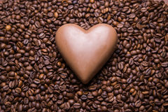 Coffee beans wallpaper with chocolate heart. Background stock photos