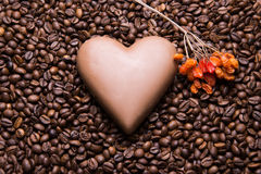 Coffee beans wallpaper with chocolate heart and viburnum berrie. Background royalty free stock image