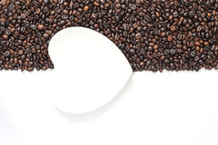 Coffee beans on white background with white saucer. Coffee beans on white background in half frame with white saucer Royalty Free Stock Photos