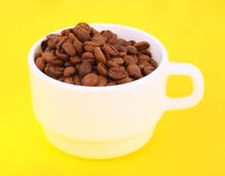 Coffee beans in a white bowl. On a yellow background Stock Image
