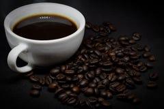Coffee beans and white ceramic coffee mug. Closeup coffee beans and white ceramic coffee mug on the dark background Stock Photography