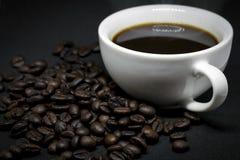 Coffee beans and white ceramic coffee mug. Closeup coffee beans and white ceramic coffee mug on the dark background Stock Image