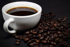 Coffee beans and white ceramic coffee mug. Closeup coffee beans and white ceramic coffee mug on the dark background Stock Photos