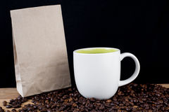 Coffee beans in white cup and brown paper bag Royalty Free Stock Images