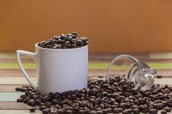 Coffee beans in white cup with clear glass. Close up Royalty Free Stock Images
