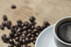 Coffee beans and white cup close up Royalty Free Stock Photos