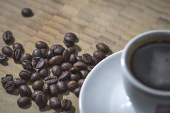 Coffee beans and white cup close up Stock Image