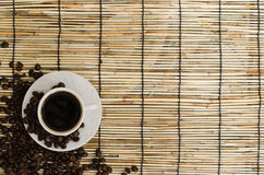 Coffee beans with white cup on mat.  royalty free stock photo