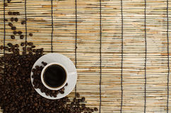 Coffee beans with white cup on mat.  Royalty Free Stock Image