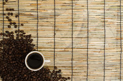 Coffee beans with white cup on mat.  royalty free stock photos