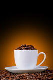 Coffee beans in a white cup on a orange background Royalty Free Stock Photography