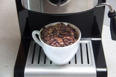 Coffee beans in a white Cup. Preparation of coffee. Coffee machine. stock photos