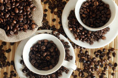 Coffee beans with a white cup and sack Stock Photography