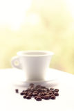 Coffee beans and white cup on a table on a yellow background Royalty Free Stock Photography