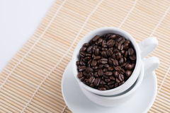 Coffee beans in white cup. Coffee beans in cup on wood background Stock Photo